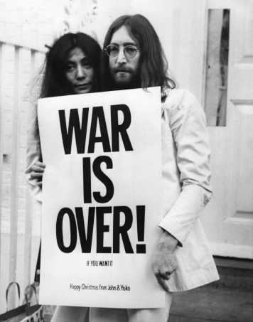John Lennon (1940 - 1980) and Yoko Ono pose on the steps of the Apple building in London, holding one of the posters that they distributed to the world's major cities as part of a peace campaign protesting against the War. 'War Is Over, If You Want It'.   (Photo by Frank Barratt/Getty Images)